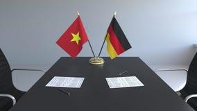 Banderas de Vietnam y de Alemania y papeles en la tabla Negociaciones y firma de un acuerdo internacional 3D conceptual metrajes