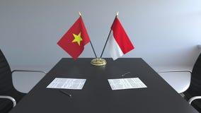Banderas de Vietnam y de Indonesia y papeles en la tabla Negociaciones y firma de un acuerdo internacional Conceptual almacen de metraje de vídeo