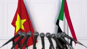 Banderas de Vietnam y de Sudán en la rueda de prensa internacional de la reunión o de las negociaciones animación 3D almacen de video