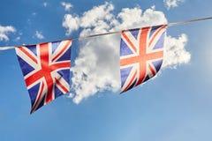 Banderas del empavesado de británicos Union Jack contra el cielo Imagenes de archivo