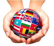 Banderas del mundo en globo y mano. Fotos de archivo