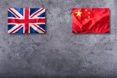 Banderas del Reino Unido y de la China en fondo concreto imagenes de archivo