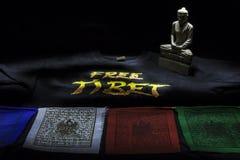 Banderas del rezo con la camiseta de Tíbet y la estatua libres de Buda Foto de archivo libre de regalías