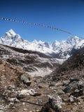 Banderas del rezo con los picos Himalayan Imágenes de archivo libres de regalías