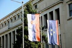 Banderas del servio y de la Vojvodina al lado de la asamblea de la Vojvodina Foto de archivo