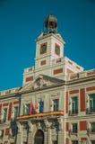 Banderas en el edificio viejo exquisito con el campanario y el reloj en Madrid foto de archivo