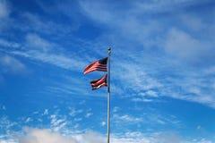 Banderas hawaianas y americanas en un fondo azul de cielo nublado imagenes de archivo