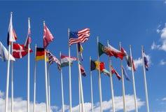 Banderas nacionales en los palos Las banderas de los Estados Unidos, de la Alemania, de la Bélgica, de la Italia, del Israel, de  fotografía de archivo