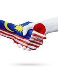 Banderas países de Malasia, Japón, concepto del apretón de manos de la amistad de la sociedad Foto de archivo libre de regalías