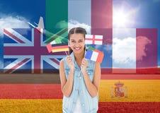 banderas principales de la lengua alrededor de la mujer joven con las banderas con el avión detrás en campo Fotografía de archivo libre de regalías