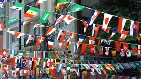 Banderas que agitan en el cielo en el fondo de la ciudad Cámara lenta, banderas de muchos estados en una ubicación almacen de video