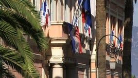 Banderas que vuelan desde fuera de un edificio en Córcega almacen de metraje de vídeo