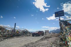 Banderas tibetanas coloridas con el cielo azul en el punto de visi?n a lo largo del camino a la reserva de naturaleza de Yading foto de archivo