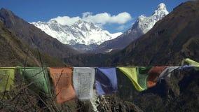 Banderas tibetanas del rezo contra el pico de montaña nevoso blanco en la región de montañas Himalayan, Nepal de Everest almacen de video