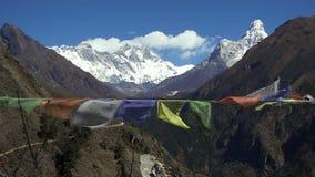 Banderas tibetanas del rezo contra el pico de montaña nevoso blanco en la región de montañas Himalayan, Nepal de Everest almacen de metraje de vídeo