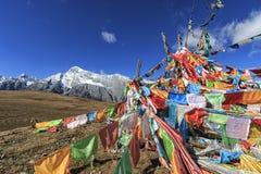 Banderas tibetanas del rezo en primero plano y Jade Dragon Snow Mountain en fondo foto de archivo libre de regalías