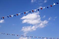 Banderas triangulares decorativas coloridas debajo del cielo azul con las nubes imagen de archivo