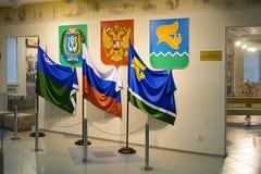 Banderas y emblemas del distrito autónomo de Rusia, de Khanty-Mansi y de la ciudad de Langepas en el pasillo del museo y del ce d imagen de archivo libre de regalías