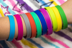 Bandes élastiques en main Les filles remettent avec des bracelets faits de caoutchouc b Photographie stock