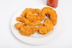 Bandes de poulet dans le plat blanc avec la bouteille de sauce chaude Photo libre de droits