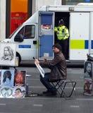 bandes dessinées d'une peinture d'artiste de rue et travaux de portraits dans la place de Leicester tandis qu'une police équipe d image libre de droits