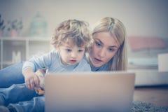 Bandes dessinées de observation de fils de maman et de bébé sur l'ordinateur portable Photo stock