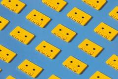 Bandes jaunes de cassette sonore sur le fond bleu Concept créatif de rétro technologie Photographie stock libre de droits