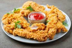 Bandes panées de poulet avec le ketchup de tomate d'un plat blanc Aliments de préparation rapide sur le fond brun foncé photo libre de droits