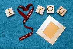 Bandherz, Liebesaufschrift auf hölzernen Würfeln, Fotorahmen und lizenzfreies stockbild