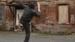 Bandido agresivo en el entrenamiento negro de la máscara y de la capilla a luchar con el bate de béisbol almacen de metraje de vídeo