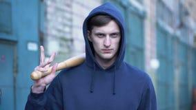 Bandido encapuçado irritado que guarda o bastão, preparando-se para a luta, juventude criminosa, ataque video estoque