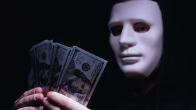 Bandido encapuchado en la máscara que cuenta los dólares, rescate para la víctima del secuestro, mafia metrajes