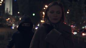 Bandido fêmea na máscara e capa que roubam a bolsa da mulher na rua escura da cidade, crime video estoque
