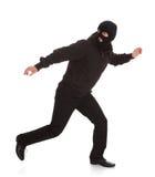 Bandido na máscara preta que corre afastado Fotografia de Stock Royalty Free