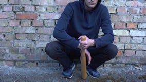 Bandido novo que senta-se perto da parede de tijolo que guarda o bastão, área do alto-crime do hooligan da cidade video estoque