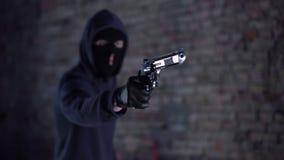 Bandido que amenaza con el arma, gángster que sostiene el arma, robo, agresión almacen de metraje de vídeo