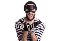 Bandido que muestra la joyería robada y la sonrisa imagen de archivo libre de regalías