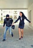 Bandido que rouba o saco da mulher imagem de stock