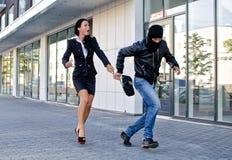 Bandido que rouba o saco da mulher fotografia de stock