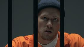 Bandido seguro que mastiga o palito atrás das barras da prisão, cabeça perigosa da máfia video estoque