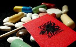 Bandiera albanese con il lotto delle pillole mediche isolate sul nero Immagine Stock Libera da Diritti