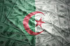 Bandiera algerina d'ondeggiamento variopinta su un fondo dei soldi del dollaro Immagini Stock Libere da Diritti