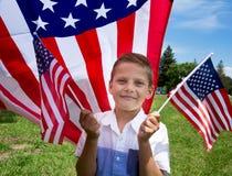 Bandiera americana adorabile della tenuta del ragazzino all'aperto il bello giorno di estate Fotografia Stock Libera da Diritti