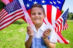 Bandiera americana adorabile della tenuta del ragazzino all'aperto il bello giorno di estate Immagini Stock Libere da Diritti