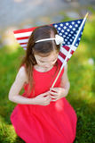 Bandiera americana adorabile della tenuta della bambina all'aperto il bello giorno di estate Immagine Stock