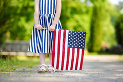 Bandiera americana adorabile della tenuta della bambina all'aperto il bello giorno di estate Immagine Stock Libera da Diritti