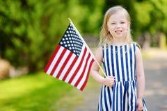 Bandiera americana adorabile della tenuta della bambina all'aperto il bello giorno di estate Immagini Stock