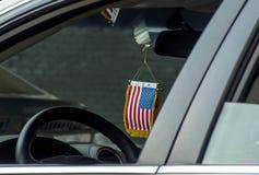 Bandiera americana che appende in automobile Fotografia Stock