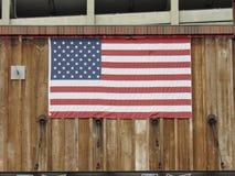 Bandiera americana che appende sull'esterno della costruzione fotografia stock libera da diritti