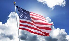 Bandiera americana che ondeggia in cielo blu luminoso Fotografia Stock